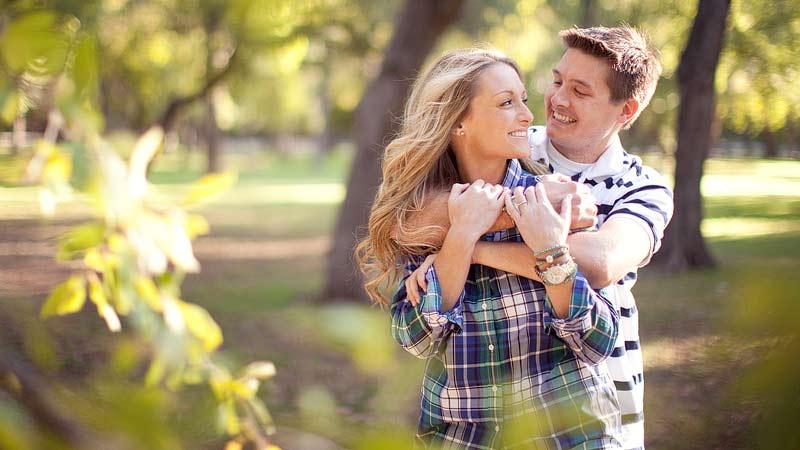 matrimonio-pareja-joven-sonriendo-abrazandose-al-aire-libre